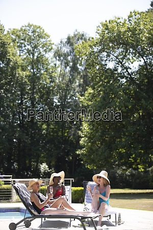 senior women friends sunbathing drinking champagne