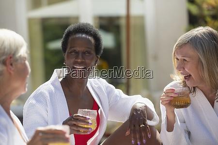 happy senior women friends enjoying cocktails