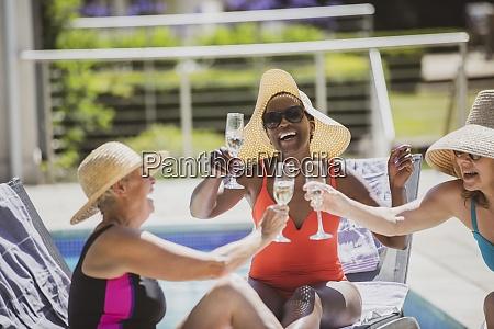 happy senior women friends drinking champagne