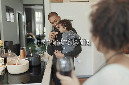 father cooking and feeding baby daughter