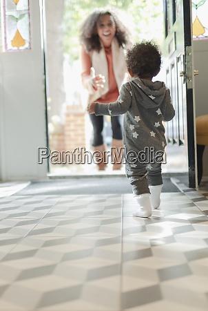 happy baby daughter running to greet