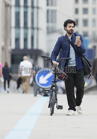 businessman with smart phone walking bicycle