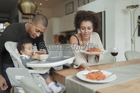 couple eating spaghetti and feeding baby