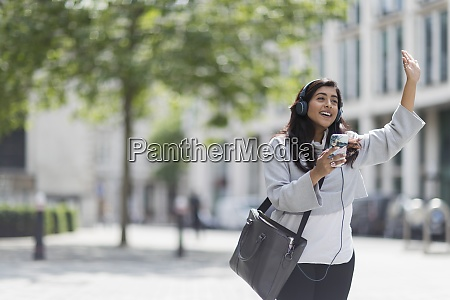 businesswoman with smart phone hailing taxi