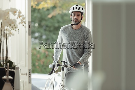 man with bicycle returning home through