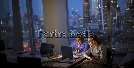 business people working late at laptop