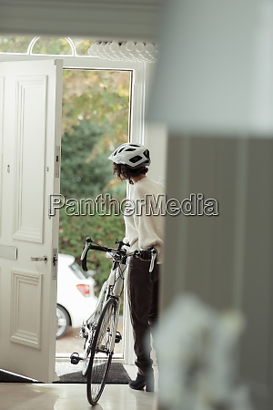 woman with bicycle returning home through