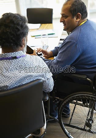 businessman in wheelchair talking with colleague