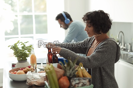 woman unloading groceries in kitchen while