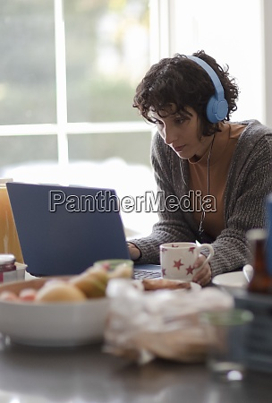 woman with headphones working from home