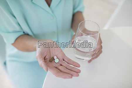 senior woman taking vitamins with water