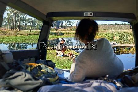 young woman in car watching boyfriend