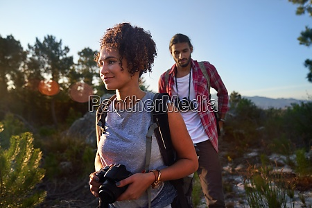 young couple hiking with camera and