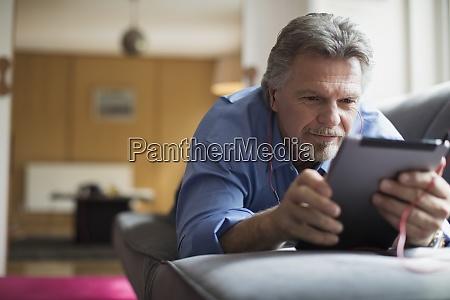 senior man using headphones and digital