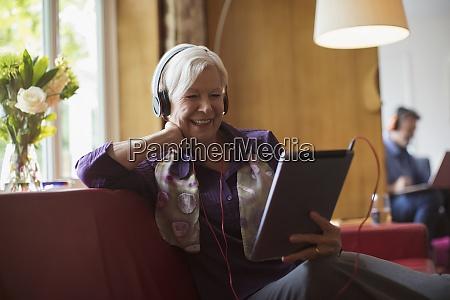 happy senior woman using headphones and