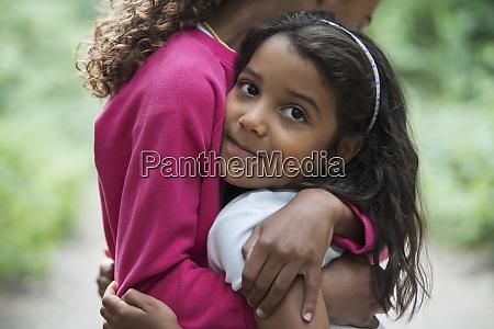 portrait cute girl hugging sister