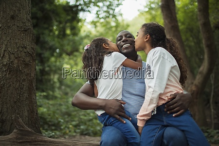 happy affectionate daughters kissing father below