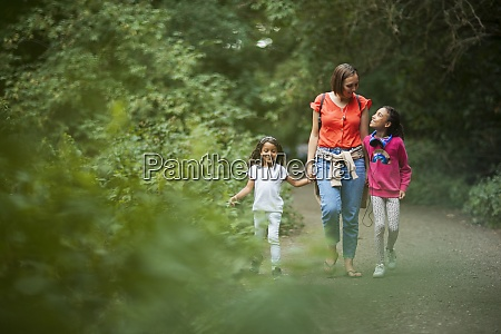 mother and daughters walking on path