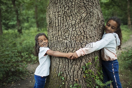 serene sisters hugging tree trunk in