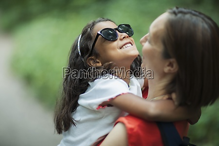 happy mother holding daughter in sunglasses
