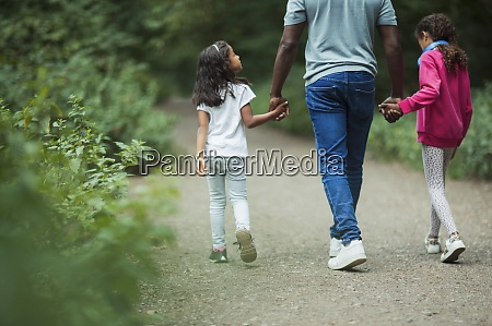 father and daughters holding hands walking
