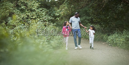 father and daughters holding hands on