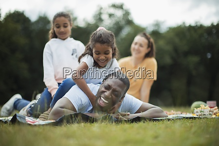 happy playful family on picnic blanket