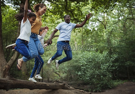 carefree family jumping off fallen log