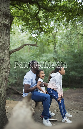 happy father and daughters sitting on