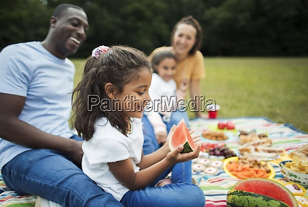 happy girl eating watermelon with family