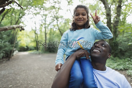 portrait father carrying daughter gesturing peace