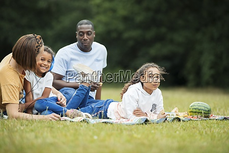 family relaxing and enjoying picnic in