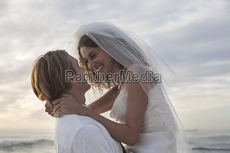 romantic newlyweds at beach against sky