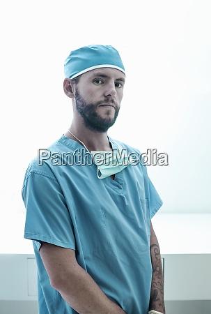 confident male surgeon standing at illuminated