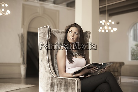 thoughtful young woman with magazine sitting
