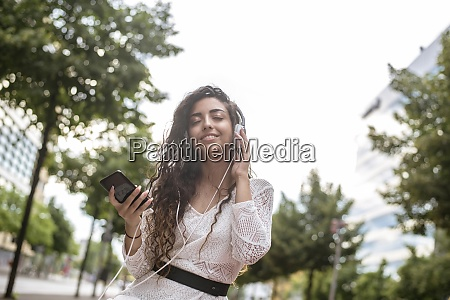 young woman holding mobile phone with