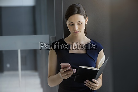 confident businesswoman holding diary using smart