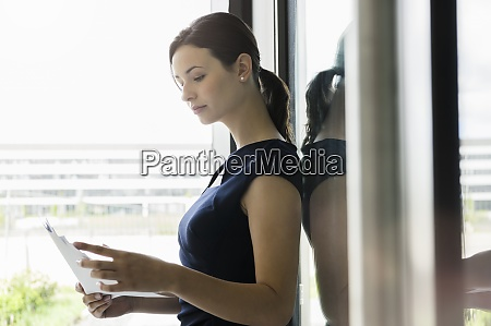 businesswoman reading documents while standing by