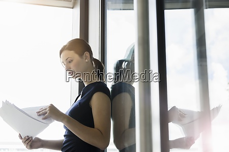 businesswoman analyzing reports while standing by