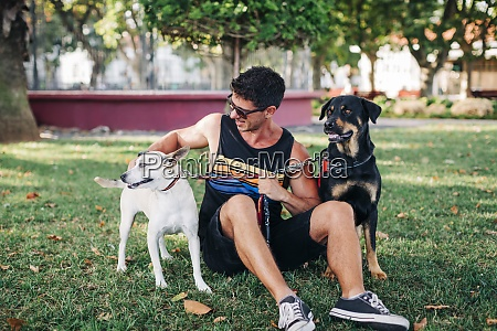 man wearing sunglasses with dogs sitting