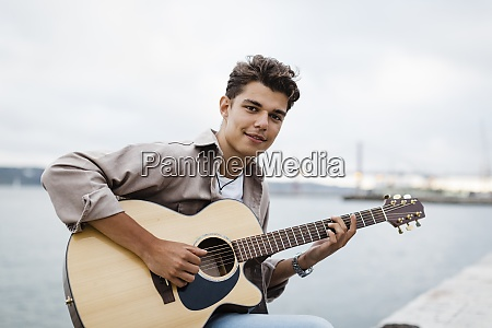 handsome young man playing guitar while