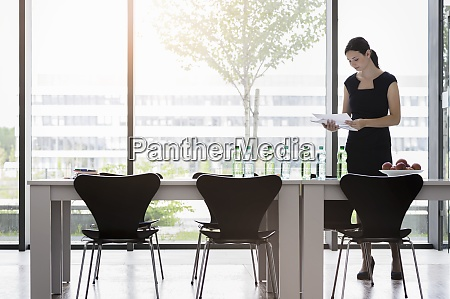 businesswoman analyzing reports while standing at