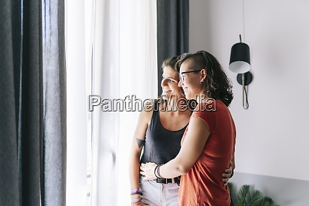 friends looking through window while standing