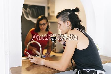 young woman washing dish while friend