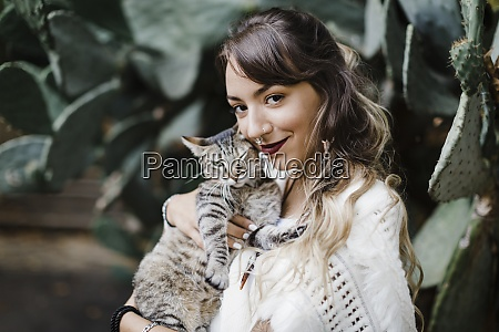 young woman smiling while holding cat