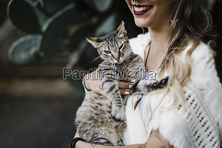 smiling woman holding cat while standing