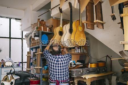 senior man hanging guitar in a