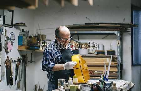 man polishing guitar while standing by