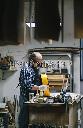 craftsman making guitar while standing at