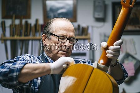 senior men polishing guitar while standing